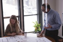 Business colleagues discussing over blueprints in office — Stock Photo