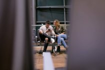 Couple using mobile phone in waiting area at airport — Stock Photo