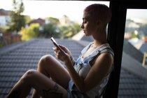 Elegante donna che utilizza il telefono cellulare vicino alla finestra a casa . — Foto stock
