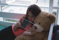 Fille avec ours en peluche en utilisant une tablette numérique en verre dans la chambre — Photo de stock
