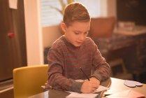 Мальчик рисует на бумаге дома — стоковое фото