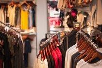 Variedades de vestuário pendurado em exposição no shopping — Fotografia de Stock