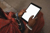 Mid section of maasai man in traditional clothing using digital tablet — Stock Photo