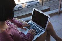Donna usando il portatile nel balcone a casa — Foto stock