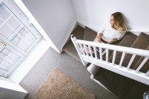 Продуманий жінка, використовуючи ноутбук, сидячи на сходах вдома — стокове фото