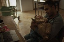 Father holding his baby in living room at home — Stockfoto