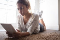 Woman using digital tablet while lying on the floor at home — Stock Photo