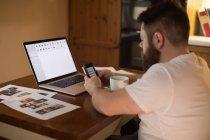 Homme handicapé utilisant un téléphone portable tout en travaillant sur un ordinateur portable à la maison — Photo de stock