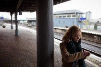 Giovane donna in piedi alla piattaforma ferroviaria controllando il tempo nel suo orologio intelligente — Foto stock