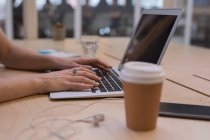 Ejecutivo femenino usando portátil en el escritorio en la oficina - foto de stock