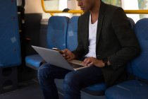 Mid section of businessman using mobile phone and laptop while travelling in bus — Stock Photo