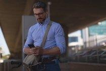 Улыбающийся человек, с помощью мобильного телефона под мостом — стоковое фото