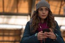 Mujer reflexiva utilizando el teléfono móvil en la estación de tren - foto de stock