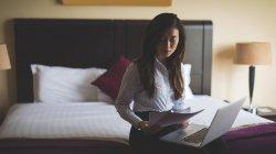 Mujer de negocios leyendo documentos mientras trabaja en el ordenador portátil en la habitación de hotel - foto de stock