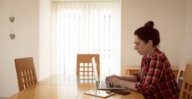 Красива жінка в окуляри, використовуючи ноутбук на дому — стокове фото