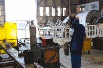 Welder wearing welding helmet in workshop — Stock Photo