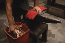 Blacksmith holding log sticks in workshop — Stock Photo