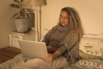 Mature woman using laptop in bedroom at home — Stockfoto