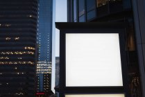Tablero de anuncio en blanco cerca de la calle en la noche - foto de stock
