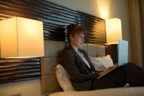 Mujer de negocios usando el portátil en una cama en la habitación de hotel - foto de stock