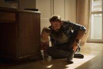 Счастливые отец и сын играют дома — стоковое фото