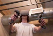 Vista a basso angolo del dirigente maschile utilizzando cuffie realtà virtuale con controller in ufficio . — Foto stock