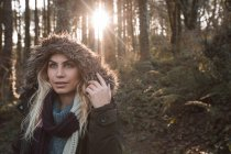 Young woman in hoodie standing at forest — Stock Photo