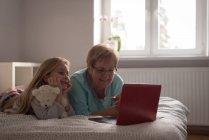 Abuela y su hija utilizando la computadora portátil en la habitación en la casa - foto de stock