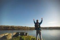 Vista posterior de hombre excursionista de pie con los brazos en el campo - foto de stock