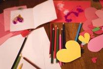 Close-up de coração forma artesanato e lápis colorido no chão de madeira — Fotografia de Stock