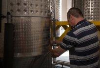 Male worker working near distillery in gin factory — Stock Photo