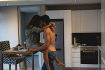 Couple embracing each other in kitchen at home — Stock Photo
