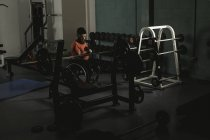 Handicapped man on wheelchair working out with dumbbell in gym — Stock Photo