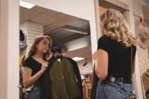 Rear view of girl checking jacket in front of the mirror — Stock Photo