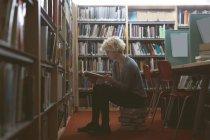 Junge Frau liest ein Buch in der Bibliothek — Stockfoto