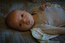 Портрет милого ребенка, лежащего на кровати — стоковое фото