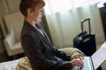 Businesswoman using laptop on bed in hotel room — Stock Photo