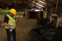 Konzentrierter Arbeiter mit seinem Handy auf dem Schrottplatz — Stockfoto