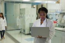 Female scientist using laptop at corridor — Stock Photo
