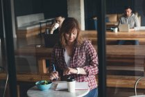 Предприниматель, писать на дневник в кафетерии в офисе — стоковое фото