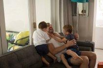 Padre jugando con sus hijos en la sala de estar en casa - foto de stock
