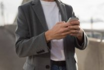 Mid section of man using mobile phone — Stock Photo