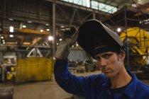 Portrait of confident welder holding welding helmet in workshop — Stock Photo