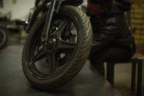 Meccanico che ripara moto nel garage — Foto stock