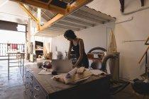 Giovane donna artigiana che lavora in laboratorio interno . — Foto stock