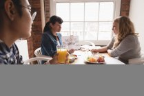 Female executives discussing with each other while having breakfast in the meeting room — Stock Photo