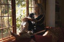 Femme mûre réfléchie assise sur le rebord de la fenêtre à la maison — Photo de stock