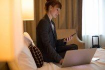 Mujer de negocios utilizando el teléfono móvil mientras trabaja en el ordenador portátil en la habitación de hotel - foto de stock