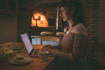 Femme à l'aide d'ordinateur portable tout en prenant son petit déjeuner à la maison — Photo de stock