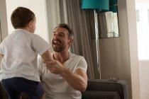 Père et fils jouent ensemble dans le salon à la maison — Photo de stock